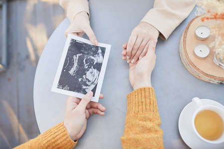 Close-up of couple sitting at the table with tea holding hands and looking at first ultrasound of their baby