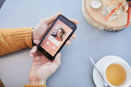 Close-up of man looking at photo of beautiful girl while using online dating app on his mobile phone