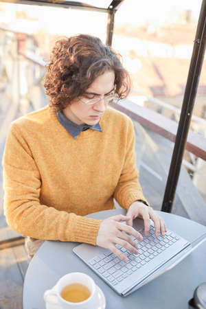 Young man with curly hair in eyeglasses sitting at the table in coffee shop and working online on laptop 免版税图像