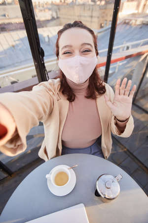 Selfie portrait of young woman in protective mask waving at camera on her mobile phone in coffee shop