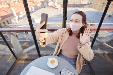 Young blogger in mask leading live stream on her mobile phone while standing in elegant restaurant