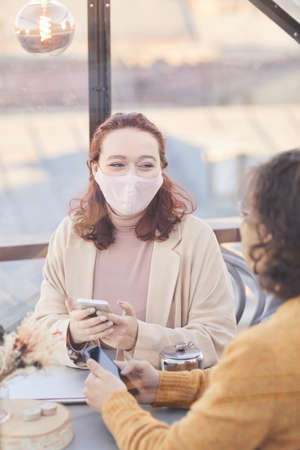 Young couple in protective masks sitting at the table in cafe and talking to each other 免版税图像