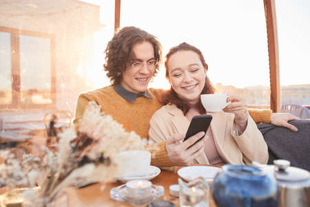 Happy young couple spending time together watching photos on mobile phone and remembering happy moments together