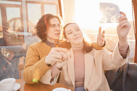 Young family looking at ultrasound image of their baby while sitting in cafe
