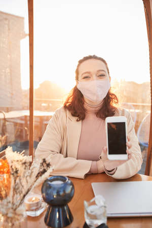 Portrait of blogger in protective mask showing the screen of her mobile phone and looking at camera while working at the table