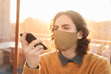 Young man in protective mask listening to audio message on his mobile phone 免版税图像