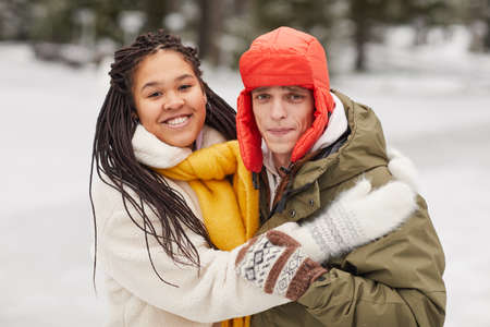 Portrait of young multiethnic couple embracing each other and smiling at camera standing outdoors