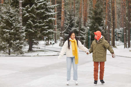 Happy multiethnic couple skating on skating rink in winter forest during winter holiday