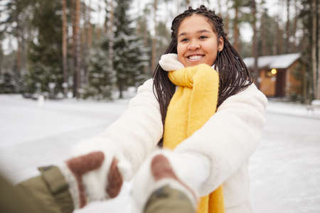 Young African woman having fun in winter day outdoors together with her friend