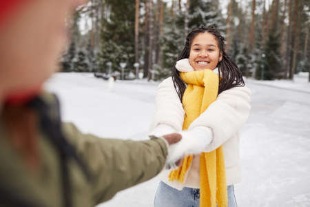African happy woman having fun together with her boyfriend outdoors in winter day