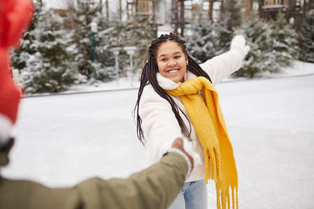 Happy African woman having fun with her friend during their walk in winter forest