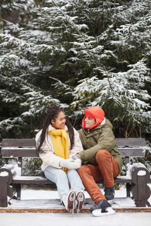 Multiethnic young couple resting on bench after skating in winter in the park