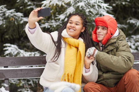 Young happy woman making selfie on her mobile phone with her boyfriend while they sitting on bench in winter 免版税图像