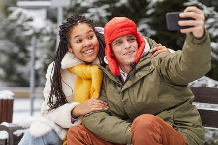 Young man making selfie portrait on his mobile phone with woman while they sitting on bench in winter park