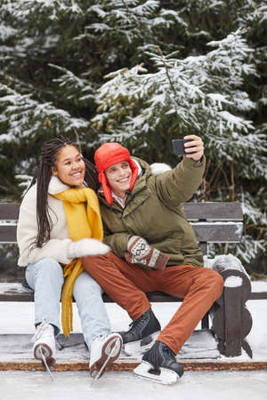 Young couple sitting on bench and making selfie portrait on mobile phone after skating in winter park