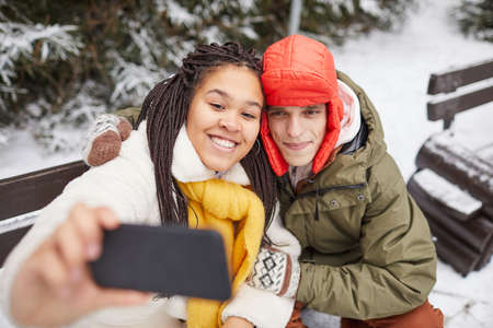 Young happy woman posing at camera of her mobile phone together with man while they sitting on bench in winter 免版税图像