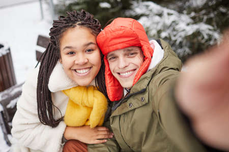 Happy young couple smiling at camera of mobile phone in winter day outdoors 免版税图像