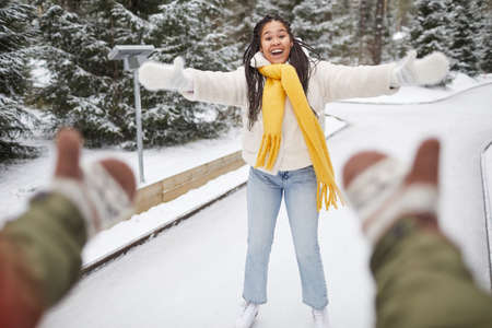 Happy woman skating on skating rink with her boyfriend who catching her 免版税图像