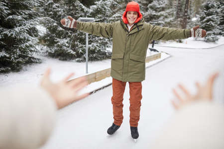Happy young man in warm clothing skating on skating rink in winter in the park