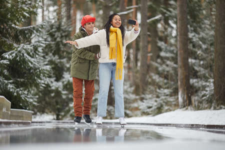 Young woman making selfie portrait on mobile phone while skating together with her boyfriend outdoors in winter