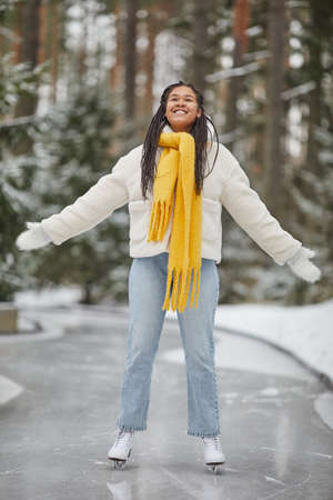 Happy African woman in warm clothing enjoying her time on skating ring in winter