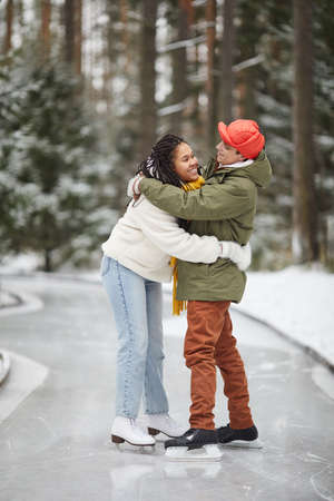 Happy young couple embracing each other standing on skating rink outdoors in winter 免版税图像