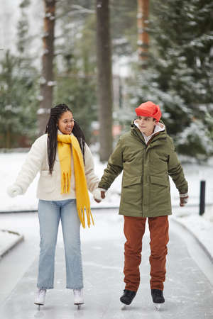 Young couple skating together holding hands and talking in outdoor skating rink