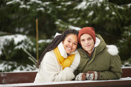Portrait of young couple embracing and smiling at camera sitting at the table with snowy trees in the background 免版税图像