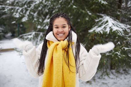 Portrait of young African woman in yellow warm scarf smiling at camera standing outdoors in winter day