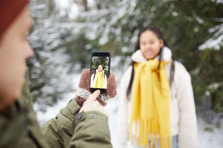 Close-up of young man holding mobile phone and photographing the woman who posing against the snowy trees in the forest 免版税图像