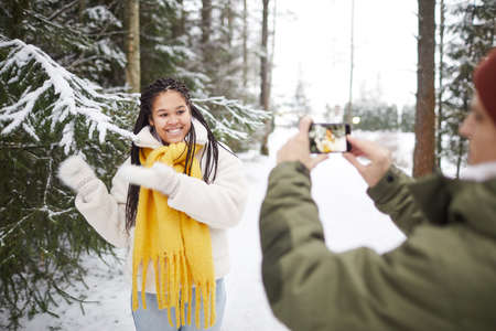 Happy woman smiling and posing at camera while man making photo on mobile phone in the forest 免版税图像