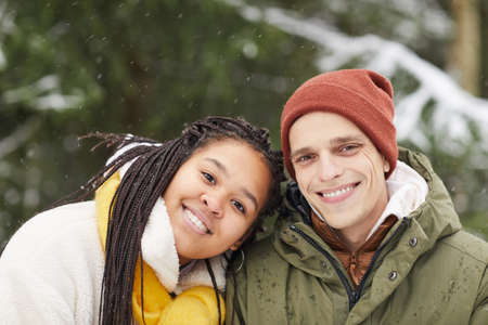 Winter portrait of multiethnic young couple smiling at camera outdoors 免版税图像