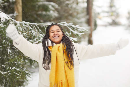 African young woman in warm clothing happy with winter during her walk in the forest 免版税图像