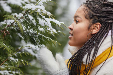 Side view of African young woman looking at fir tree with snow enjoying the winter weather