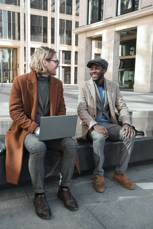 Young businessman with laptop talknig to his colleague while they sitting in the city