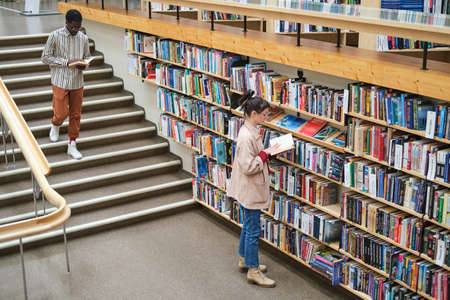 Young people choosing books and reading them in the library Banque d'images