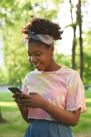 African happy woman talking online using her mobile phone while standing in the park