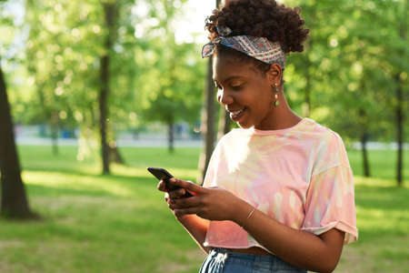 African young woman reading a message on mobile phone and smiling while standing outdoors