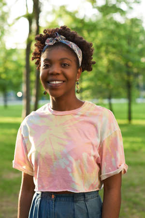 Portrait of African young woman smiling at camera while standing in the park
