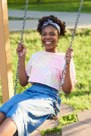 Portrait of African happy woman smiling at camera while riding on a swing in the park