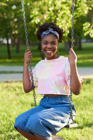 Portrait of African young woman smiling at camera while sitting on a swing in the park