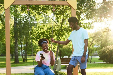 African happy couple riding on a swing and using mobile phone while spending time in the park Stockfoto