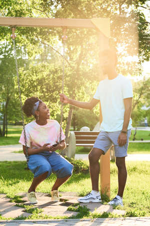 Happy African couple riding on a swing and talking in the park