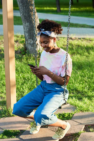 African smiling woman sitting on a swing and using mobile phone outdoors