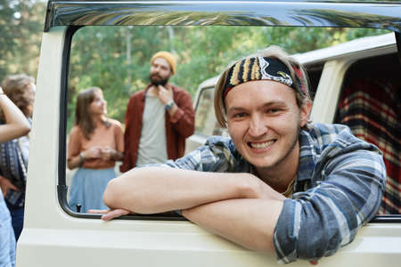 Portrait of guy smiling at camera sitting in the van with his friends in the background Stockfoto