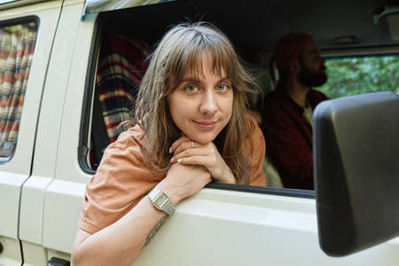 Portrait of young woman looking at camera while travelling by bus together with her friends