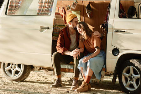 Young couple sitting in the van and embracing each other they enjoying their vacations