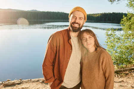 Portrait of young couple smiling at camera standing near the lake and enjoying their travelling Stockfoto