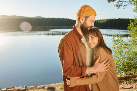 Young happy couple embracing each other standing on the nature with lake in the background Stockfoto