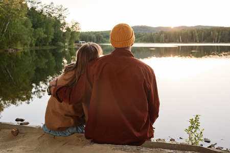 Rear view of couple in warm clothing embracing and enjoying the beautiful views of the lake outdoors